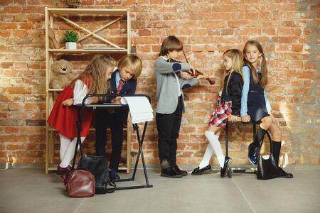 Grupo de niños que pasan tiempo juntos después de la escuela. Amigos guapos descansando después de clases antes de comenzar a hacer los deberes. Interior de loft moderno. Horario escolar, amistad, educación, concepto de unión. Foto de archivo