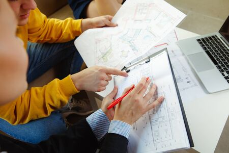 Interior designer working with young couple. Lovely family and professional designer or architector discussing conept of future interior, working with colour palette, room drawings in modern office.