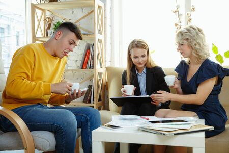 Interior designer working with young couple. Lovely family and professional designer or architecture discussing concept of future interior, working with colour palette, room drawings in modern office.