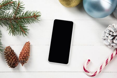 Mock up blank empty screen of smartphone on the white wooden background with colorful holidays decoration and gifts. Copyspace, negative space for your advertising. 31 of December, New Year concept.