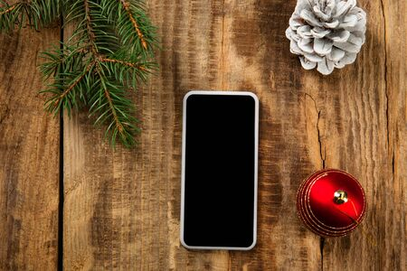 Mock up blank empty screen of smartphone on the wooden background with colorful holidays decoration and gifts. Copyspace, negative space for your advertising. 31 of December, New Year concept.
