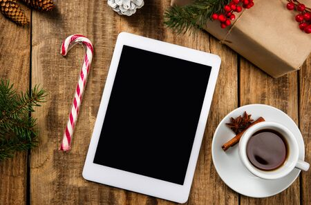 Mock up blank empty screen of tablet on the wooden background with colorful holidays decoration, tea and gifts. Copyspace, negative space for your advertising. 31 of December, New Year concept.