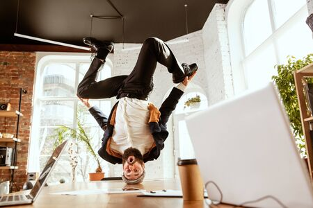 Young caucasian businessman having fun  break dance in the modern office
