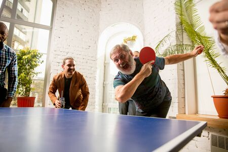 Young people playing table tennis in workplace, having fun. Friends in casual clothes play table tennis together at sunny day. Concept of leisure activity, sport, friendship, team-building, teamwork.