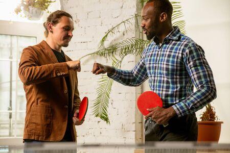 Junge Männer spielen Tischtennis am Arbeitsplatz und haben Spaß. Freunde in Freizeitkleidung spielen am sonnigen Tag zusammen Tischtennis. Konzept der Freizeitbeschäftigung, Sport, Freundschaft, Teambuilding, Teamwork.