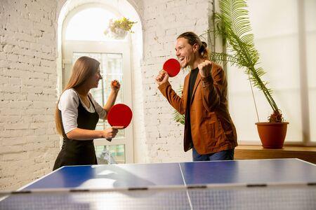 Giovani che giocano a ping pong sul posto di lavoro, divertendosi. Gli amici in abiti casual giocano a ping pong insieme alla giornata di sole. Concetto di attività per il tempo libero, sport, amicizia, team building, lavoro di squadra. Archivio Fotografico