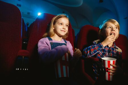 Little girl and boy, friends or sister and brother watching a film at a movie theater, house or cinema. Look expressive and emotional. Sitting alone and having fun. Friendship, family, childhood, weekend.