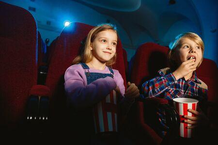 Niña y niño, amigos o hermana y hermano viendo una película en una sala de cine, casa o cine. Luce expresivo y emocional. Sentarse solo y divertirse. Amistad, familia, infancia, fin de semana.
