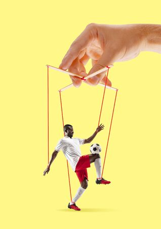 Man like a puppet in somebodies hands on yellow background. Concept of unfair manipulation, phycology of exploitation, mental technique, motivation. Puppets and their masters. Possessive relationship. Stock Photo