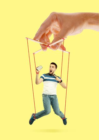 Man like a puppet in somebodies hands on yellow background. Concept of unfair manipulation, phycology of exploitation, mental technique, motivation. Puppets and their masters. Possessive relationship.