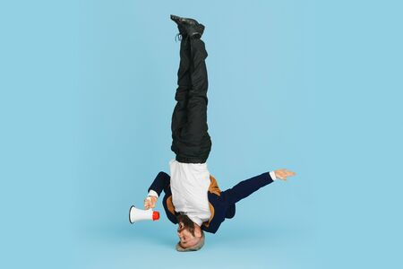 Young caucasian businessman having fun dancing break dance on blue studio background. Management, flexible, freedom, professional occupation, alternative way of modern working. Loves his job. Copyspace.