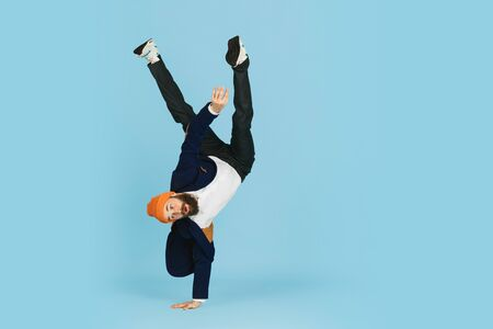 Young caucasian businessman having fun dancing break dance on blue studio background. Management, flexible, freedom, professional occupation, alternative way of modern working. Loves his job. Copyspace.