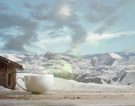 Single tea or coffee mug and landscape of mountains on background. Cup of hot drink with snowly look and cloudly sky in front of it. Warm in winter day, holidays, travel, New Year and Christmas time. 版權商用圖片