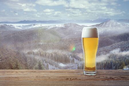 Single light beer in glass and landscape of mountains on background. Alcohole drink and sunshine look and clear sky in front of it. Warm in spring day, holidays, travel, adventure time.