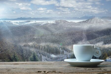 Single tea or coffee mug and landscape of mountains on background. Cup of hot drink sunshine look and clear sky in front of it. Warm in spring day, holidays, travel, adventure time.