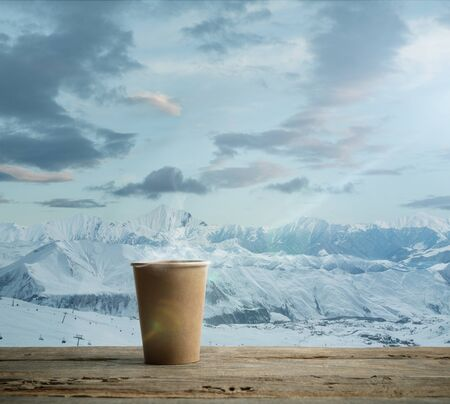 Single tea aor coffee mug and landscape of mountains on background. Cup of hot drink with snowly look and cloudly sky in front of it. Warm in winter day, holidays, travel, New Year and Christmas time.