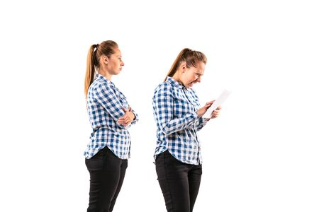 Young handsome woman arguing with herself on white studio background. Concept of human emotions, expression, mental issues, internal conflict, split personality. Half-length portrait. Negative space. Standard-Bild