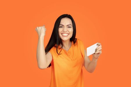 Caucasian young womans portrait on orange studio background. Beautiful female brunette model in shirt. Concept of human emotions, facial expression, sales, ad. Copyspace. Plays smartphone, win in bet. 版權商用圖片