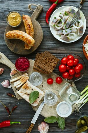 Vodka with lard, salted fish and vegetables, sausages on wooden background. Alcohol pure craft drink and traditional snack, tomatos, cabbage, cucumbers. Negative space. Celebrating food and delicious.