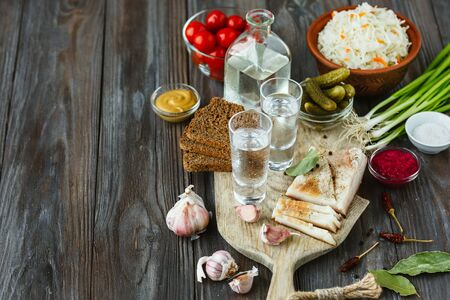 Vodka with lard, salted vegetables on wooden background. Alcohol pure craft drink and traditional snack, tomatos, cabbage, cucumbers. Negative space. Celebrating food and delicious.