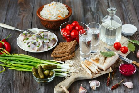 Vodka with lard, salted fish and vegetables on wooden background. Alcohol pure craft drink and traditional snack, tomatos, cabbage, cucumbers. Negative space. Celebrating food and delicious.