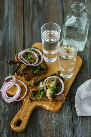 Vodka with fish and bread toast on wooden background. Alcohol pure craft drink and traditional snacks. Negative space. Celebrating food and delicious. Top view.