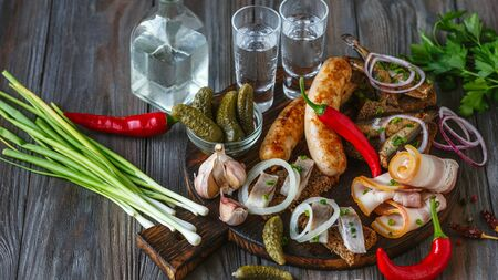 Vodka with lard, salted fish and vegetables, sausages on wooden background. Alcohol pure craft drink and traditional snack, tomatos, onion, cucumbers. Negative space. Celebrating food and delicious.