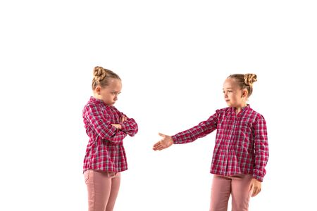 Young handsome girl arguing with herself on white studio background. Concept of human emotions, expression, mental issues, internal conflict, split personality. Half-length portrait. Negative space.