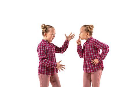 Junges hübsches Mädchen, das mit sich selbst auf weißem Studiohintergrund argumentiert. Konzept der menschlichen Emotionen, des Ausdrucks, der mentalen Probleme, des inneren Konflikts, der gespaltenen Persönlichkeit. Halbfigurenporträt. Negativer Raum.