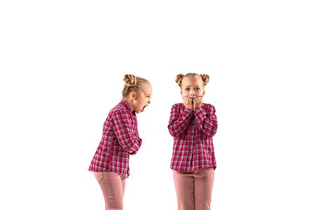 Junges hübsches Mädchen, das mit sich selbst auf weißem Studiohintergrund argumentiert. Konzept der menschlichen Emotionen, des Ausdrucks, der mentalen Probleme, des inneren Konflikts, der gespaltenen Persönlichkeit. Halbfigurenporträt. Negativer Raum. Standard-Bild
