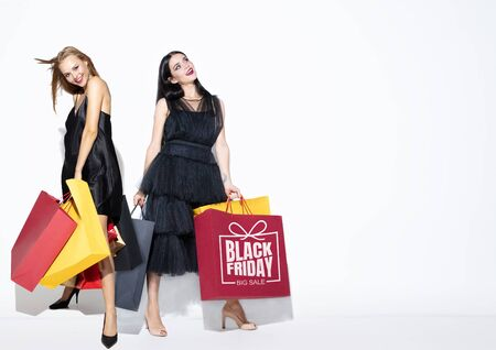 Young women in dresses shopping on white background. Attractive caucasian female models. Finance, black friday, cyber monday, sales, autumn concept. Copyspace. Smiling, posing happy.