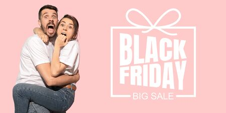 Portrait of young caucasian couple surprised and shocked of black friday on coral background. Concept of sales, black friday, cyber monday, finance, business, purchases. Online shops and payments bill.