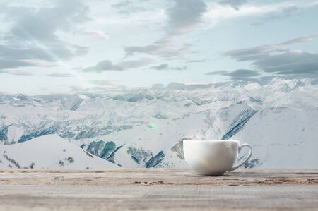 Single tea or coffee cup and landscape of mountains on background. Cup of hot drink with snowly look and cloudly sky in front of it. Warm in winter day, holidays, travel, New Year and Christmas time.