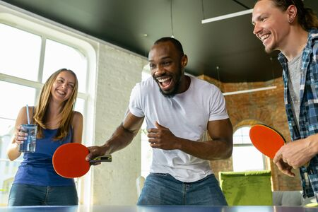 Young people playing table tennis in workplace, having fun. Friends in casual clothes play g together at sunny day. Concept of leisure activity, sport, friendship, teambuilding, teamwork. Stock Photo