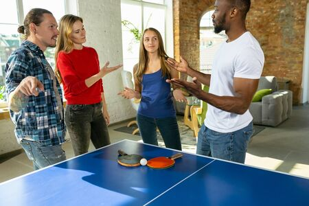Young people playing table tennis in workplace, having fun. Friends in casual clothes playtogether at sunny day. Concept of leisure activity, sport, friendship, teambuilding, teamwork.