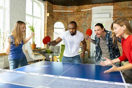 Giovani che giocano a ping pong sul posto di lavoro, divertendosi. Gli amici in abiti casual giocano insieme durante la giornata di sole. Concetto di attività per il tempo libero, sport, amicizia, team building, lavoro di squadra.