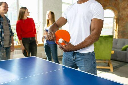 Jóvenes jugando al tenis de mesa en el lugar de trabajo, divirtiéndose. Amigos en ropa casual juegan juntos en un día soleado. Concepto de actividad de ocio, deporte, amistad, teambuilding, trabajo en equipo.
