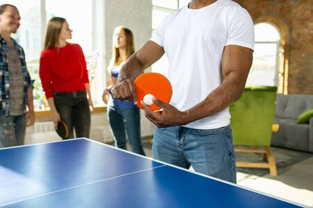 Young people playing table tennis in workplace, having fun. Friends in casual clothes play together at sunny day. Concept of leisure activity, sport, friendship, teambuilding, teamwork.