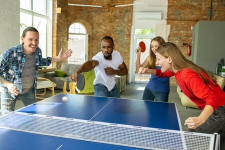 Young people playing table tennis in workplace, having fun. Friends in casual clothes play together at sunny day. Concept of leisure activity, sport, friendship, teambuilding, teamwork. Stock Photo