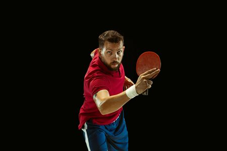 Young man plays table tennis on black studio background. Model in sportwear plays. Concept of leisure activity, sport, human emotions in gameplay, healthy lifestyle, motion, action, movement. Foto de archivo