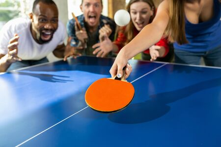 Young people playing table tennis in workplace, having fun. Friends in casual clothes play ping pong together at sunny day. Concept of leisure activity, sport, friendship, teambuilding, teamwork.