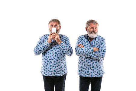 Älterer Mann, der mit sich selbst auf weißem Studiohintergrund argumentiert. Konzept der menschlichen Emotionen, des Ausdrucks, der mentalen Probleme, des inneren Konflikts, der gespaltenen Persönlichkeit. Halbfigurenporträt. Negativer Raum. Neugierig. Standard-Bild
