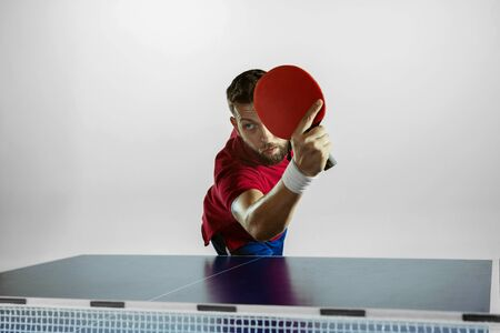 Possibility. Young man plays table tennis on white studio background. Model plays   table tennis. Concept of leisure activity, sport, human emotions in gameplay, healthy lifestyle, motion, action, movement.