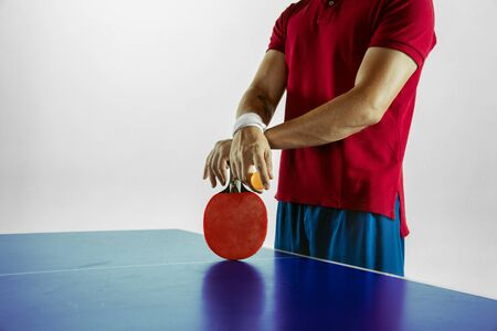 Young man plays table tennis on white studio background. Model in sportwear plays table tennis. Concept of leisure activity, sport, human emotions in gameplay, healthy lifestyle, motion, action, movement. Imagens - 133377730