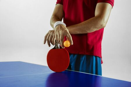 Young man plays table tennis on white studio background. Model in sportwear plays table tennis. Concept of leisure activity, sport, human emotions in gameplay, healthy lifestyle, motion, action, movement. Imagens - 133377732