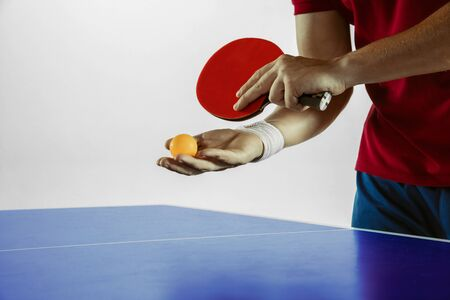 Young man plays table tennis on white studio background. Model in sportwear plays table tennis. Concept of leisure activity, sport, human emotions in gameplay, healthy lifestyle, motion, action, movement. Banque d'images