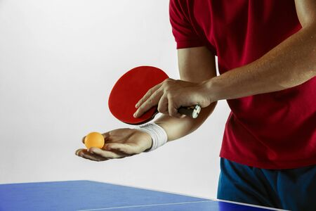 Young man plays table tennis on white studio background. Model in sportwear plays table tennis. Concept of leisure activity, sport, human emotions in gameplay, healthy lifestyle, motion, action, movement. Imagens - 133377868