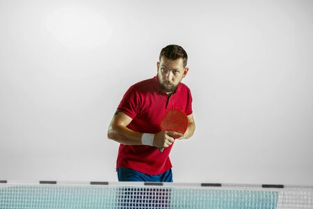 Experiences. Young man plays table tennis on white studio background. Model plays ping pong. Concept of leisure activity, sport, human emotions in gameplay, healthy lifestyle, motion, action, movement. Foto de archivo - 133479387
