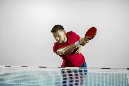 Possibilità. Il giovane gioca a ping pong su sfondo bianco per studio. La modella gioca a ping pong. Concetto di attività per il tempo libero, sport, emozioni umane nel gioco, stile di vita sano, movimento, azione, movimento.