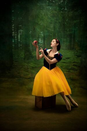 Young ballet dancer as a Snow White with poisoned apple in forest. Flexible caucasian ballerina dances like character of fairytail in bright clothes. Adorable and elegance story in motion and dancing.